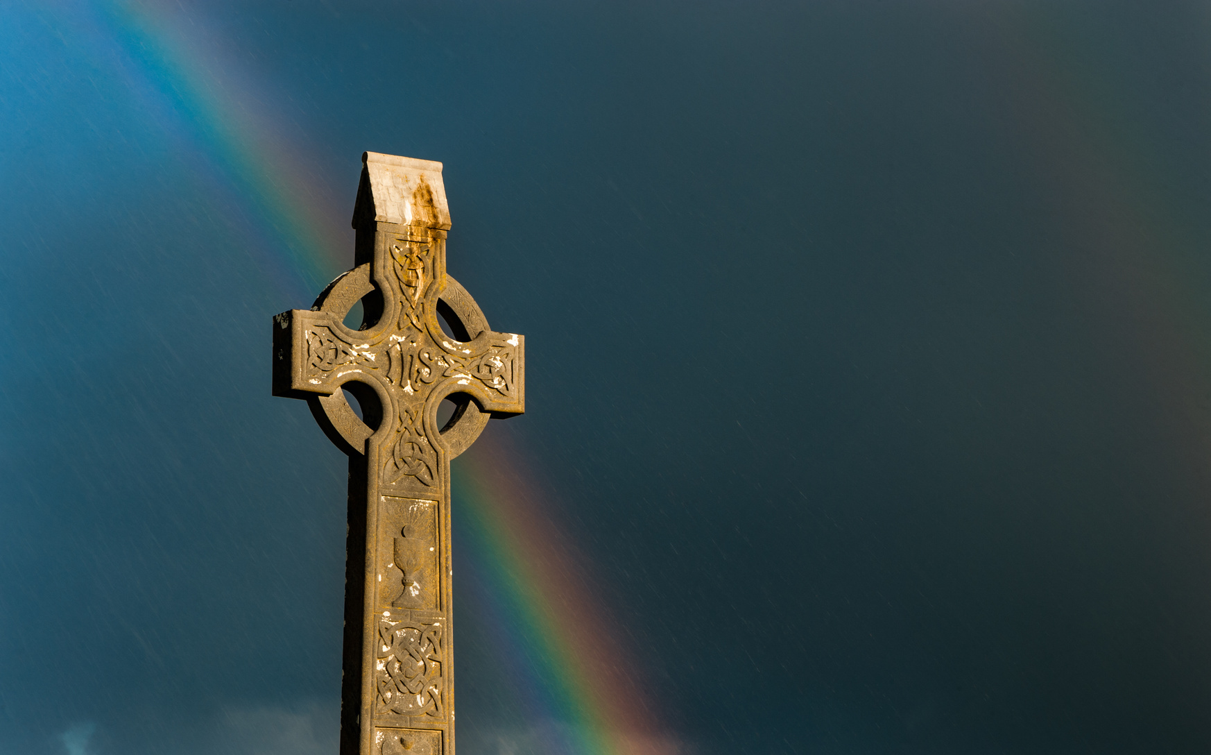 Rainbow sky behind celtic cross gravestone at sunset